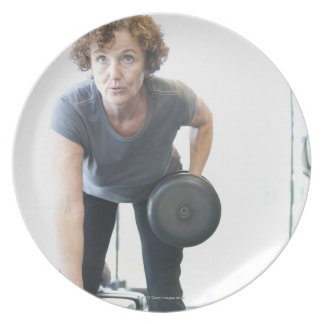Baby boomer woman working out triceps in health dinner plate