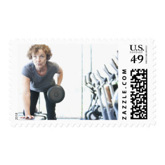 Baby boomer woman working out triceps in health postage stamps