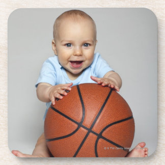 Baby boy (6-9 months) holding basketball, coaster