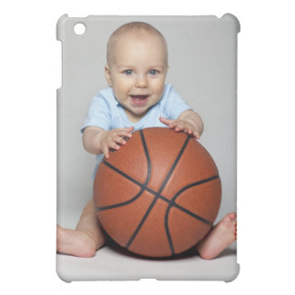 Baby boy (6-9 months) holding basketball, cover for the iPad mini