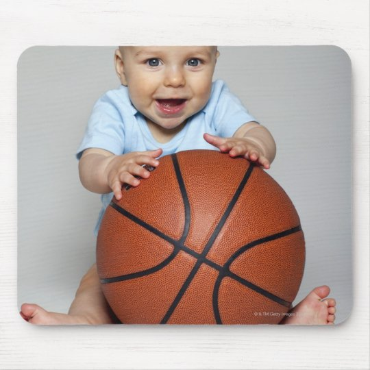 Baby boy (6-9 months) holding basketball, mouse pad