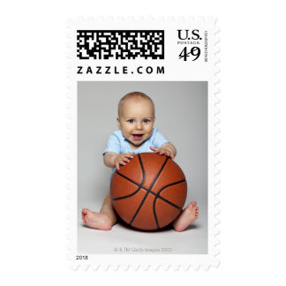 Baby boy (6-9 months) holding basketball, postage stamp