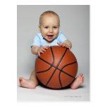 Baby boy (6-9 months) holding basketball, postcard