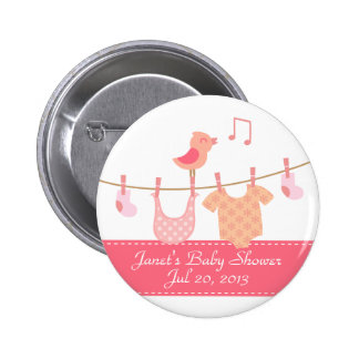 Baby clothes hanging on clothesline with pink bird buttons