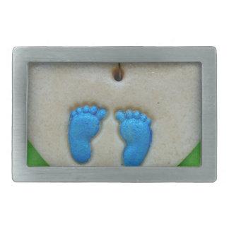 baby feet in blue rectangular belt buckle
