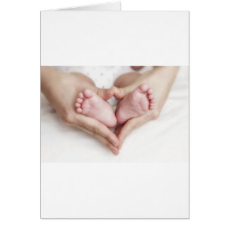 Baby feet in mother hands greeting card