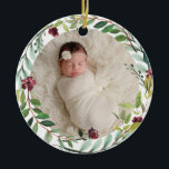 """Baby First Christmas Green Holiday Wreath Photo Ceramic Ornament<br><div class=""""desc"""">This elegant two-sided holiday photo keepsake ornament features a newborn photo of your baby girl framed by a floral watercolor holiday greenery wreath. The back of the ornament includes """"First Christmas"""" wording with custom text that can be personalized with the baby's full name and the year of their birth. Includes...</div>"""