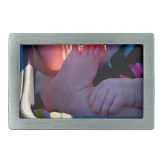 baby foot closeup with child hand holding belt buckle