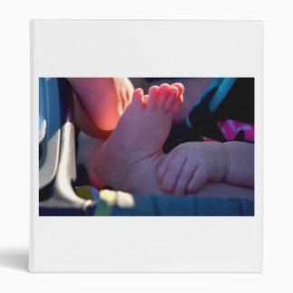 baby foot closeup with child hand holding 3 ring binder