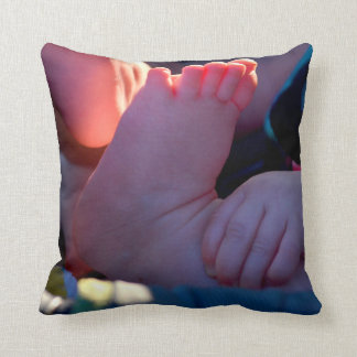 baby foot closeup with child hand holding throw pillows