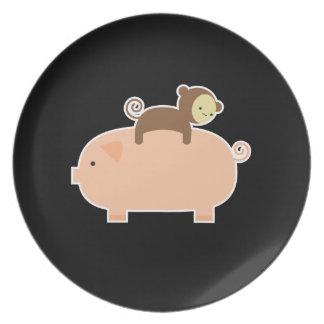 Baby Monkey Riding Backwards on a Pig Plates