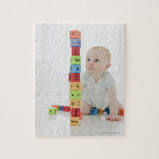 Baby on floor looking at stacked wood blocks jigsaw puzzle