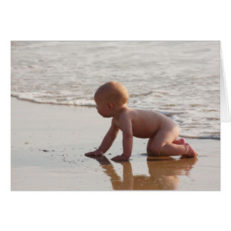 Baby playing in the sand on the beach greeting card
