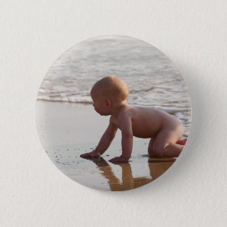 Baby playing in the sand on the beach pinback button