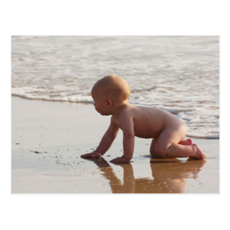 Baby playing in the sand on the beach postcards