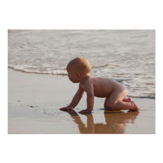 Baby playing in the sand on the beach poster