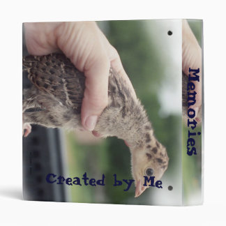 Baby turkey chick being held by a hand 3 ring binder