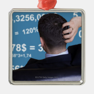Back portrait of a businessman confused with christmas tree ornament