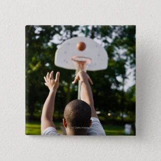 Back view of man shooting basketball outdoors button