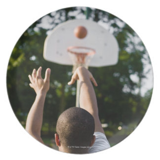 Back view of man shooting basketball outdoors dinner plate