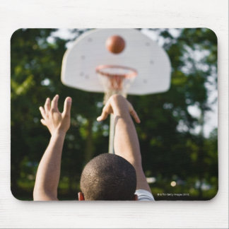 Back view of man shooting basketball outdoors mouse pad