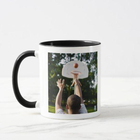 Back view of man shooting basketball outdoors mug