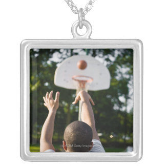 Back view of man shooting basketball outdoors necklaces
