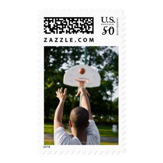 Back view of man shooting basketball outdoors postage