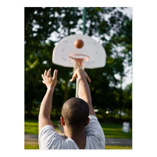 Back view of man shooting basketball outdoors postcards