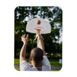 Back view of man shooting basketball outdoors rectangular magnets