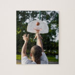 Back view of man shooting basketball outdoors puzzle