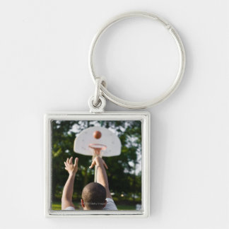 Back view of man shooting basketball outdoors Silver-Colored square keychain