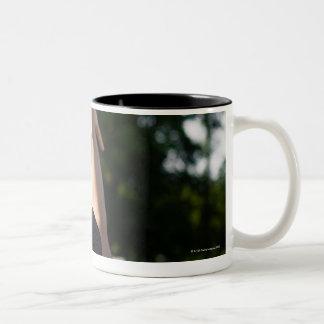 Back view of man shooting basketball outdoors Two-Tone coffee mug