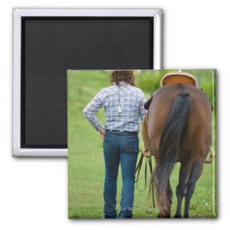 Back view of woman leading her horse 2 inch square magnet