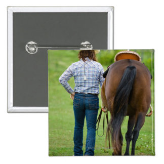 Back view of woman leading her horse 2 inch square button