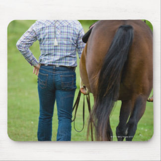 Back view of woman leading her horse mouse pad