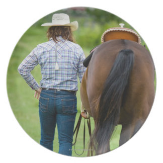 Back view of woman leading her horse dinner plate