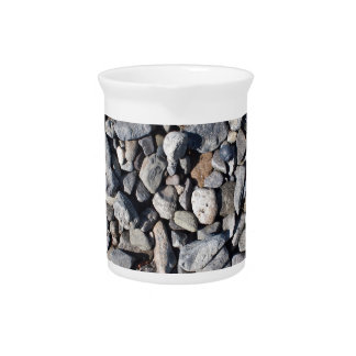 Background from small gray stones on the coast drink pitcher