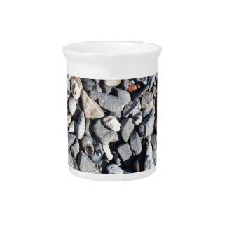 Background of gray stones and shells on the shores pitcher