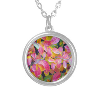 Background of vivid red leaves of autumn bush clos round pendant necklace