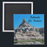 """Badlands National Park, South Dakota Magnet<br><div class=""""desc"""">The grandeur of the badlands of South Dakota is on display in this scenic photograph. The clear blue sky and the green grasslands of the mixed-grass prairie adds color to the spectacular view of this rocky outcropping. The parallel striations or ridges of the eroding buttes create layers of subtle color...</div>"""