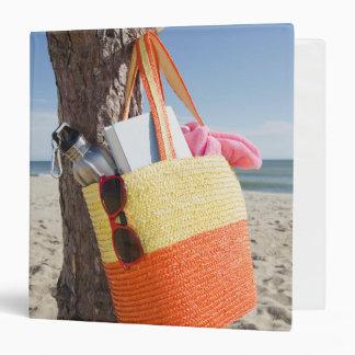 Bag Hanging On Tree Trunk At Sandy Beach Binder