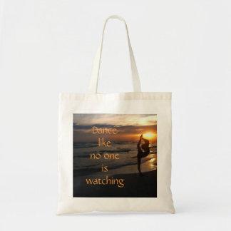 Bailarín en silueta en la playa en la bolsa de asa