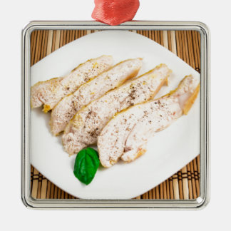 Baked chicken breast sliced on a white plate metal ornament