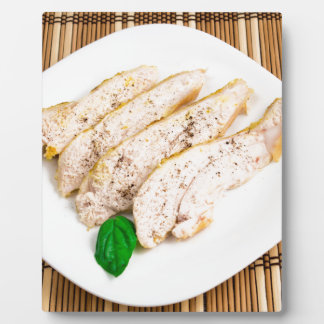 Baked chicken breast sliced on a white plate plaque