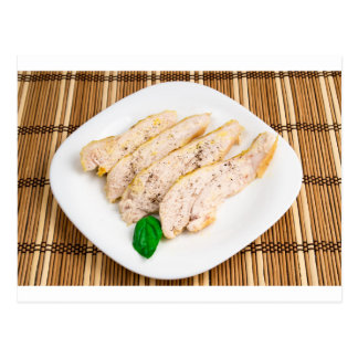 Baked chicken breast sliced on a white plate postcard