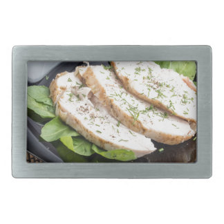 Baked slices of chicken meat on a black plate belt buckle