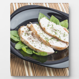 Baked slices of chicken meat on a black plate plaque