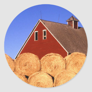 Balas de la paja al lado de un granero pegatina redonda