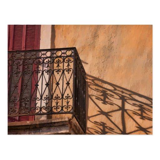Balcón bonito y puerta roja del obturador en postal